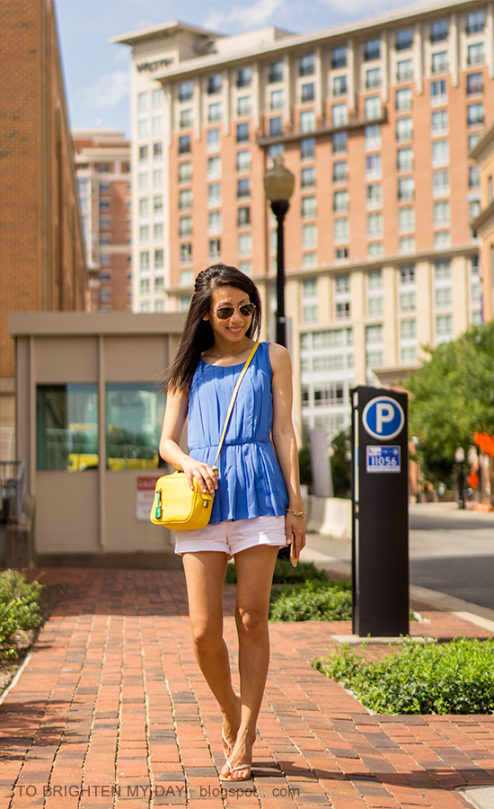 bright blue pleated sleeveless top, yellow crossbody bag, white shorts, nude flip flops