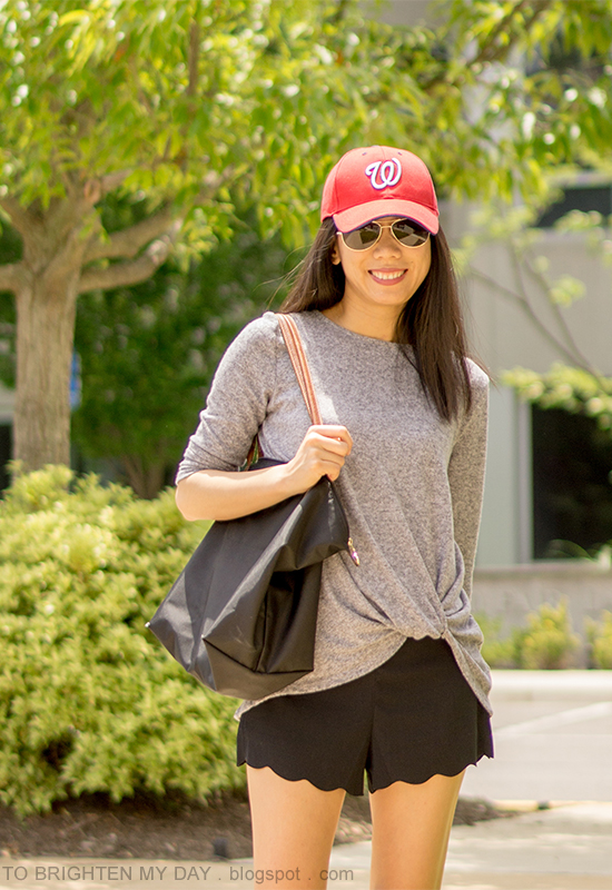 red baseball cap, gray twisted front top, black scalloped shorts, black tote
