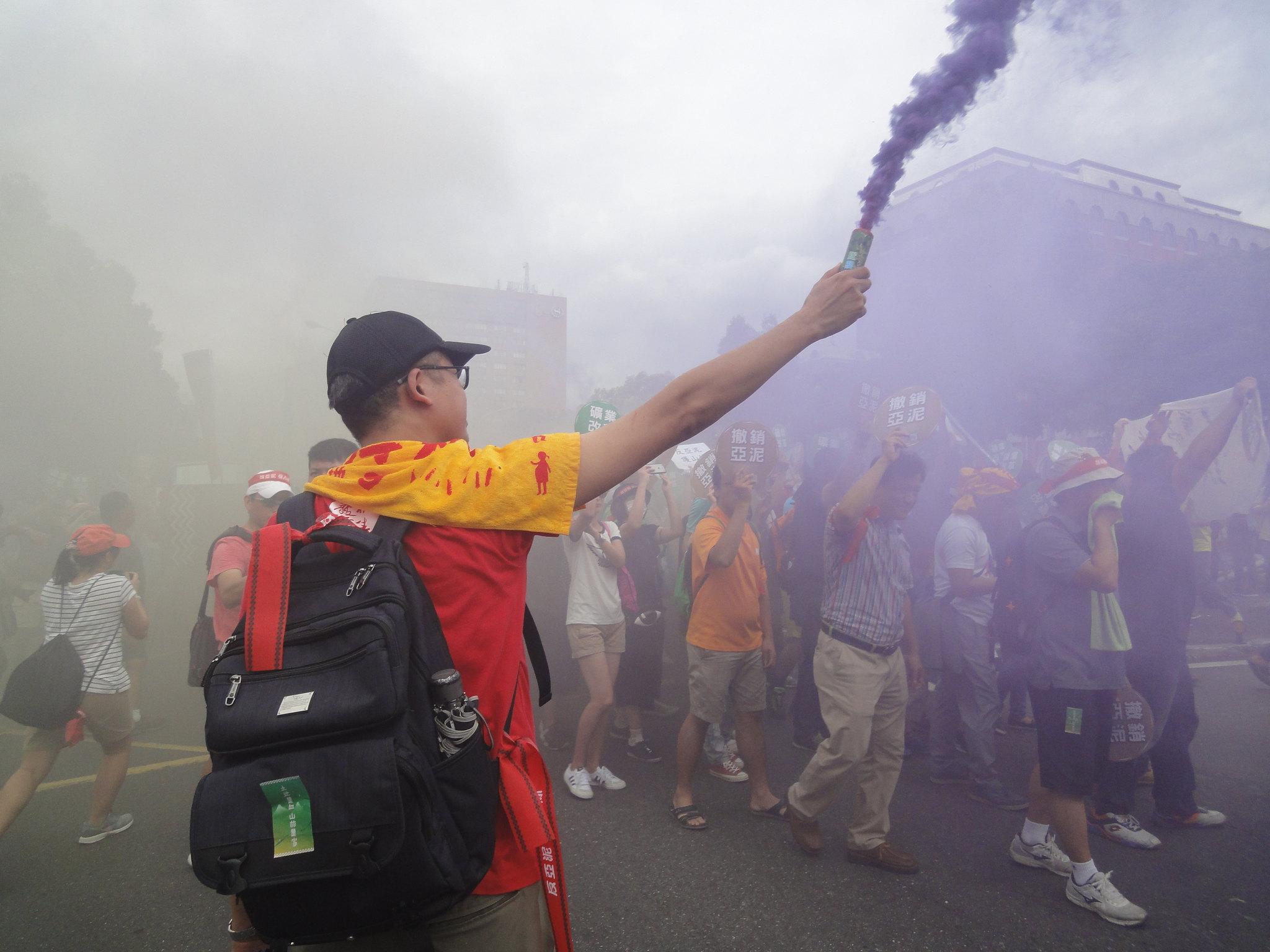 遊行參與者施放煙霧模擬亞泥炸山。(攝影:張智琦)