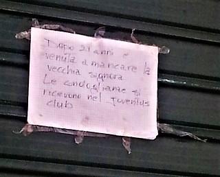 Il manifesto funebre sulla saracinesca del negozio
