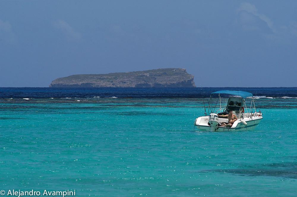 Una lancha en la costa de la Isla de Mona, con la Isla Monito de fondo