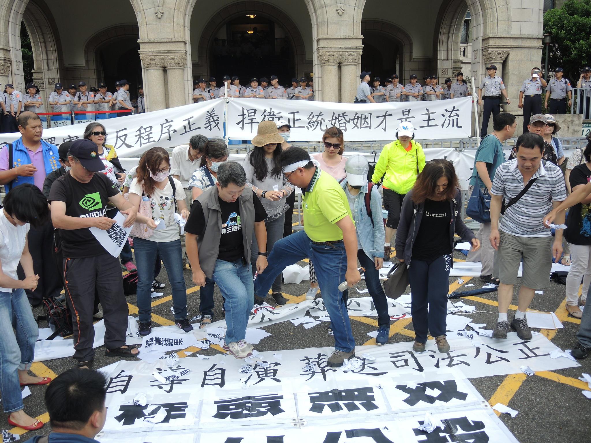 得知大法官宣告現行《民法》違憲後,下福盟將印有「釋憲結果」的紙張撕毀在地踩踏。(攝影:曾福全)