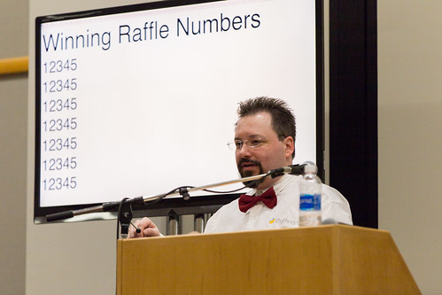 Man at lectern in front of screen displaying 'Winning Raffle Numbers: 12345 12345 12345 12345', photo (used by permission) by Mike Pirnat at the PyCon PyLadies auction in 2017