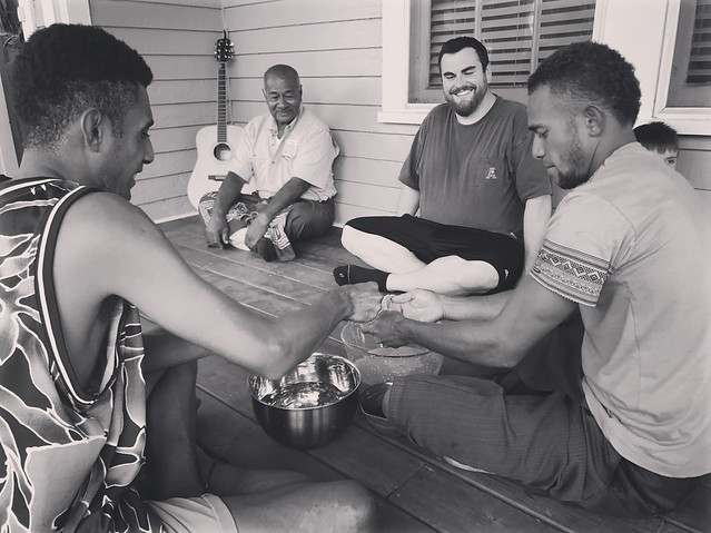 Bale Uate, Tui Mali, Zach Thornton and Nemani Baleinayaca sit on the front porch of a home for a traditional Fijian ceremony.