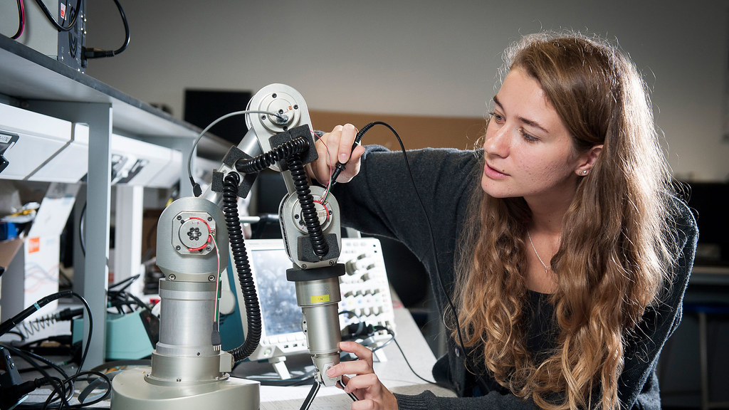 A student works on a robotic arm