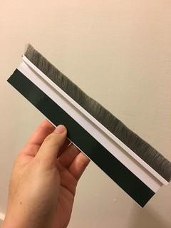 門縫填補毛刷條,後面有背膠,這塊是剪下來剩下的(我買 91cm 的,我們家的門大概只需要用 73cm 左右,貼太滿門關不起來)