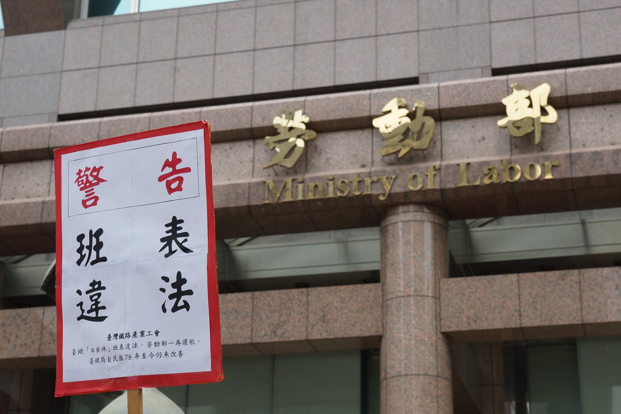 """工会成员高举""""班表违法""""。(摄影:王颢中)"""