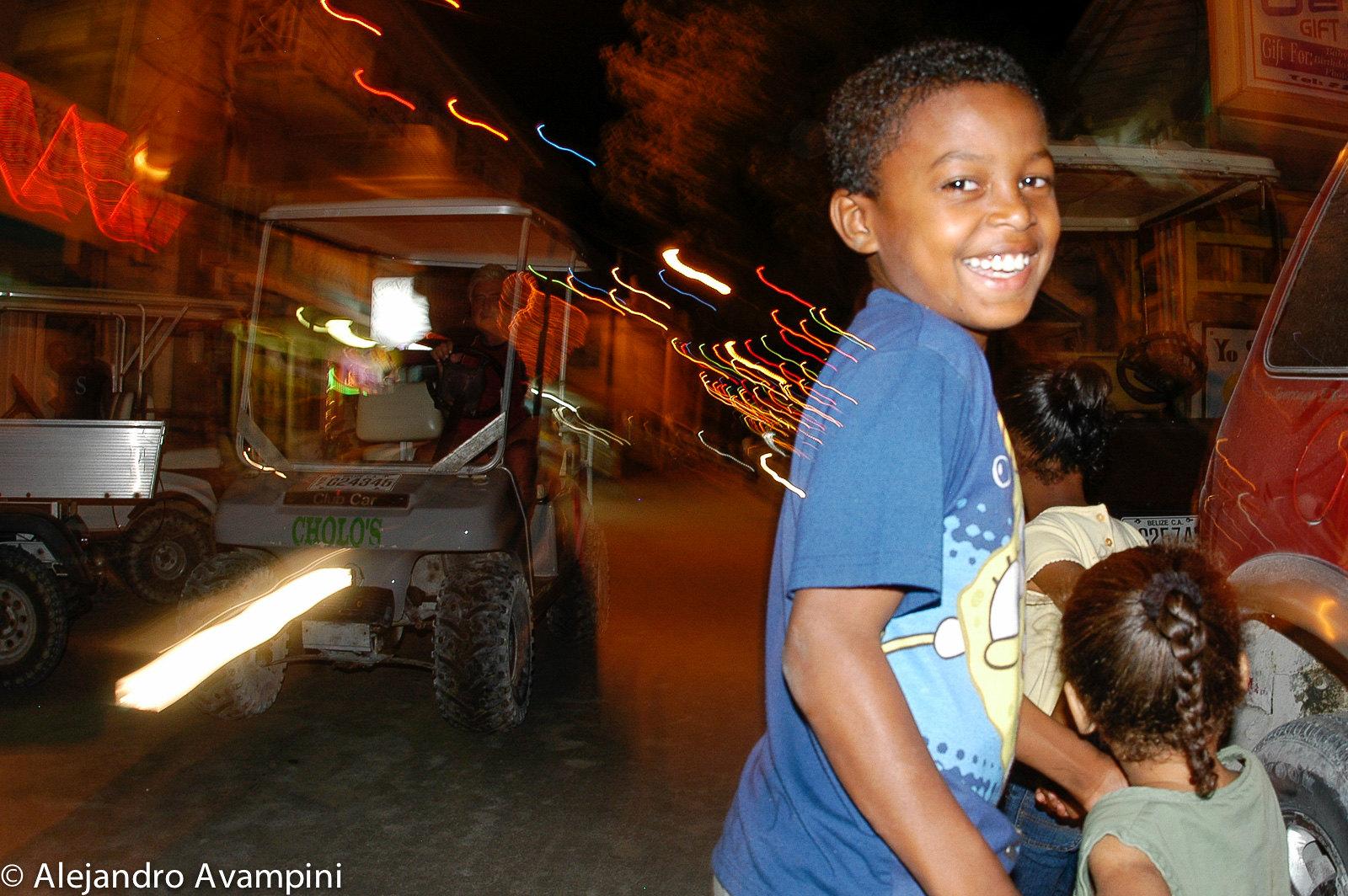 Niños diviertiendose y un carrito eléctrico en las calles de Ambergris - Belice