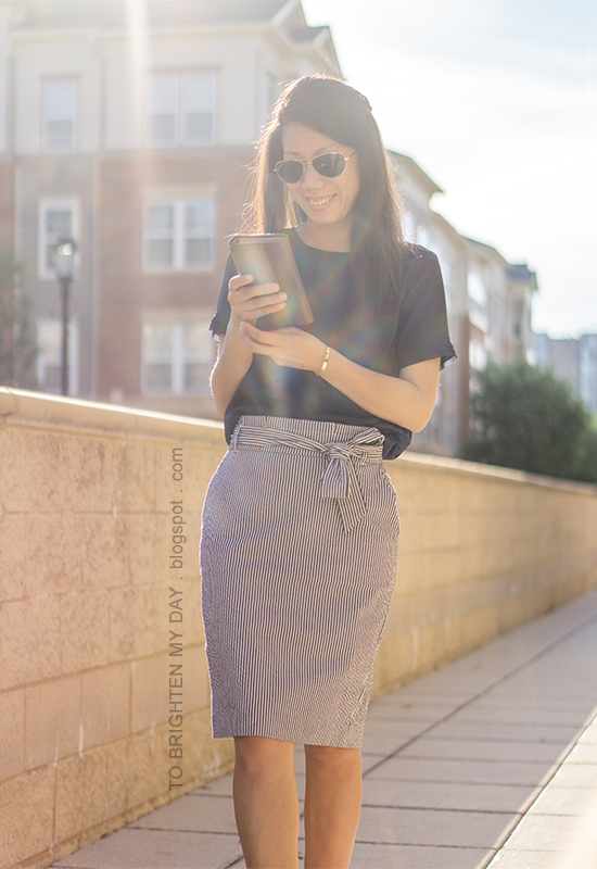 navy silky top, striped paper bag pencil skirt with bow tie, taupe clutch