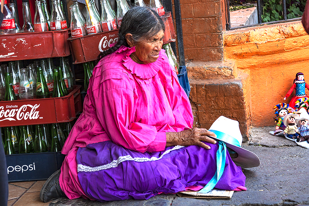 Indian woman on ground with cases of Coke and Pepsi--Tepotzotlan