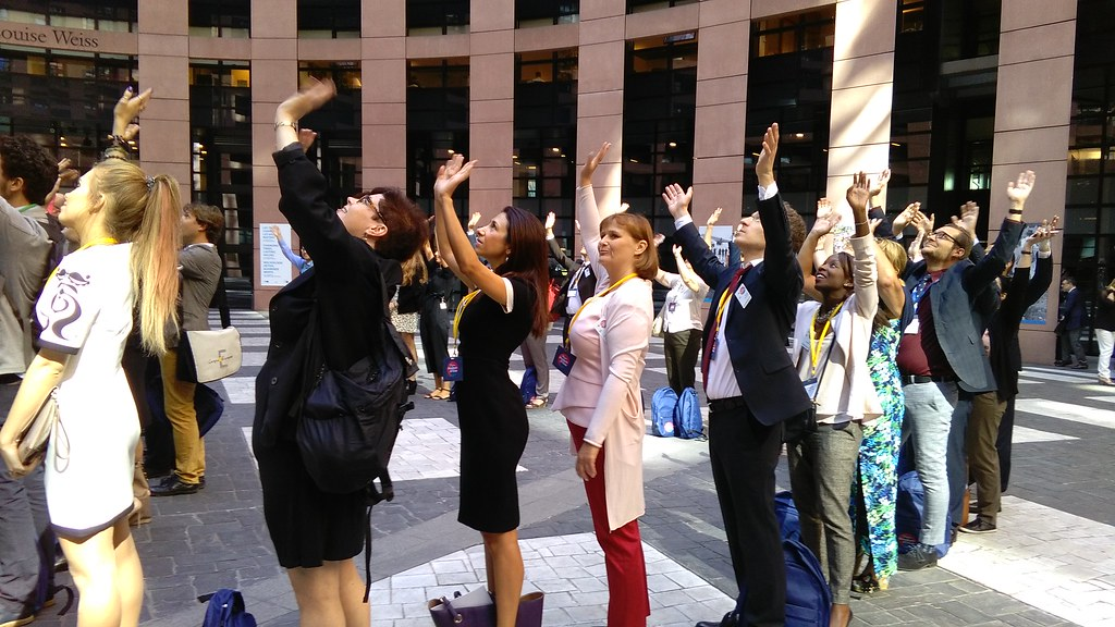 group of people with hands up taking a group picture in the European Parliament