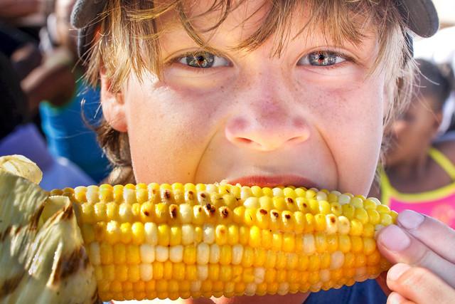 快乐的男孩吃玉米棒子