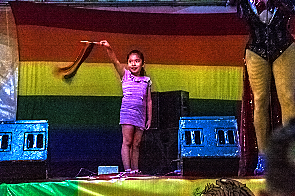 Girl waving rainbow flag on stage--Mexico City