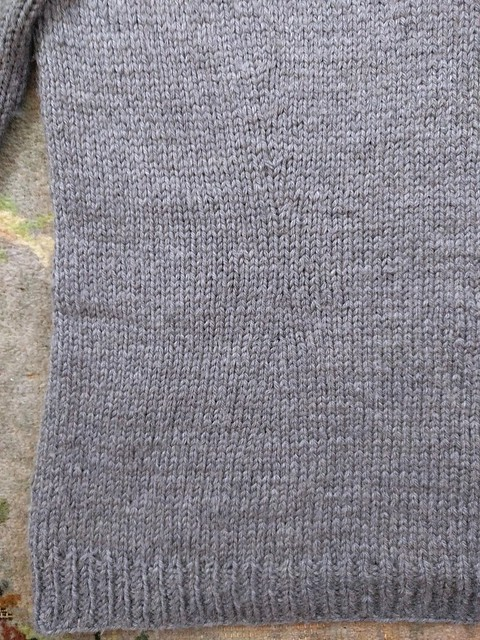 Grey handknit jumper with waist darts.