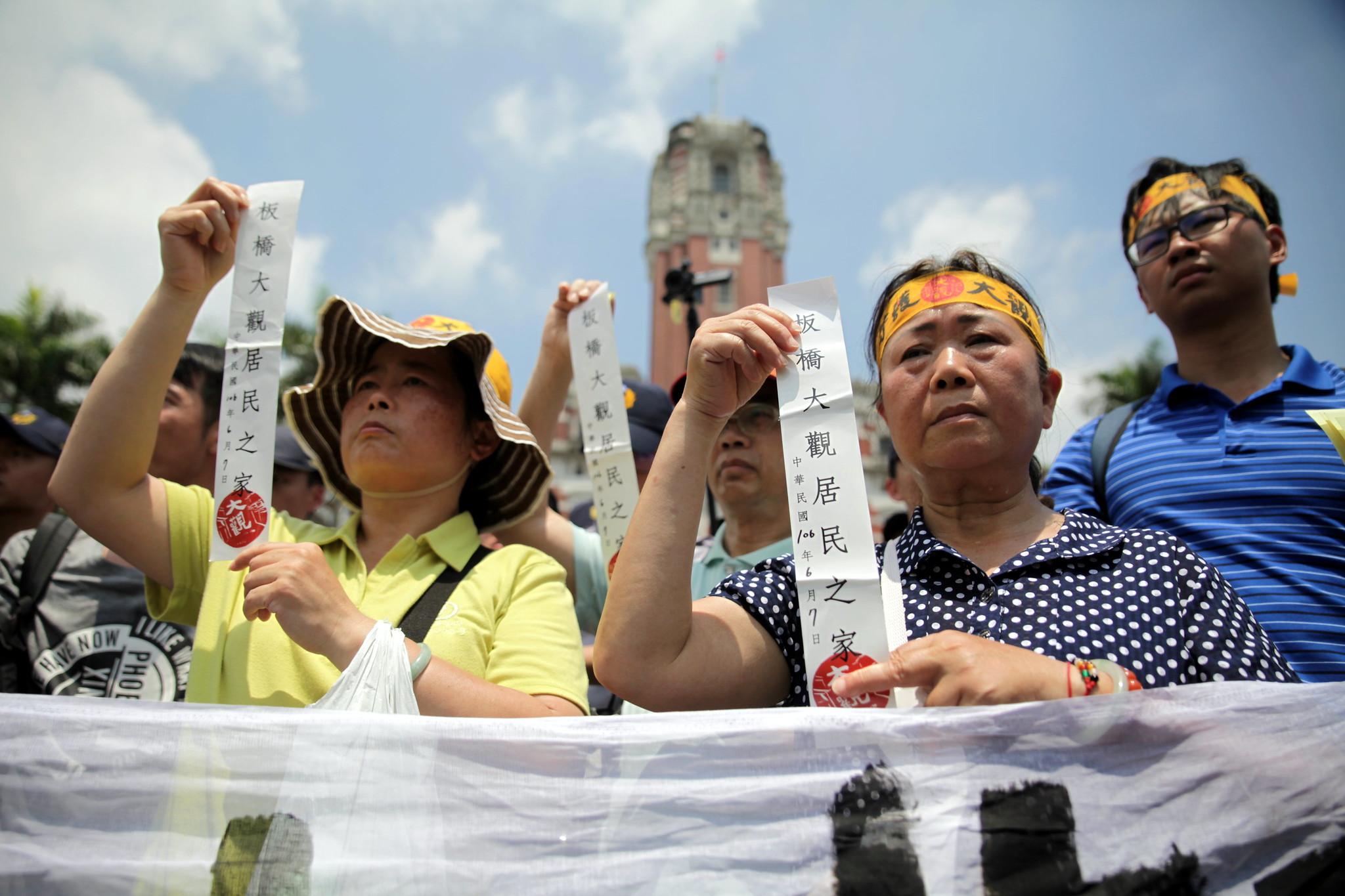 大觀居民在總統府前貼上「板橋大觀居民之家」的貼紙,表達訴求。