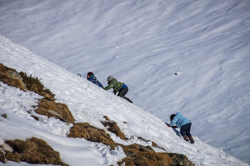 Niños trepando por la nieve