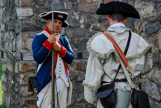 A Revolutionary War re-enactor holds historical weapon.