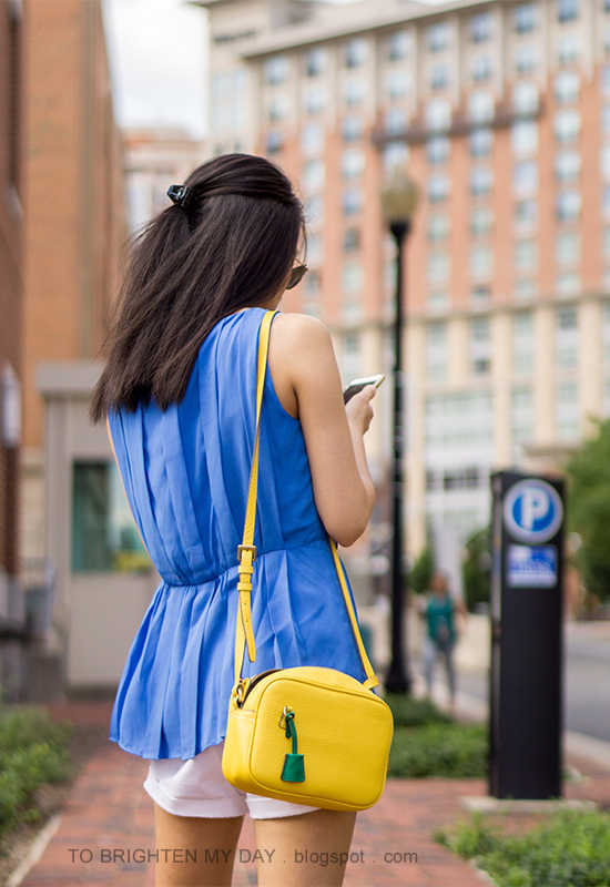 bright blue pleated sleeveless top, yellow crossbody bag, white shorts