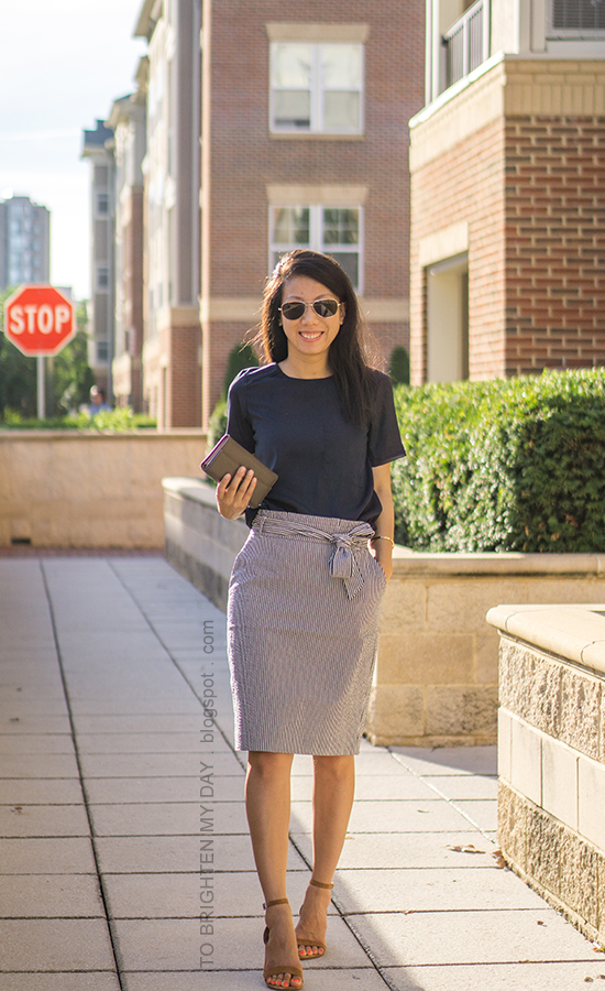navy silky top, striped paper bag pencil skirt with bow tie, taupe clutch, brown suede sandals