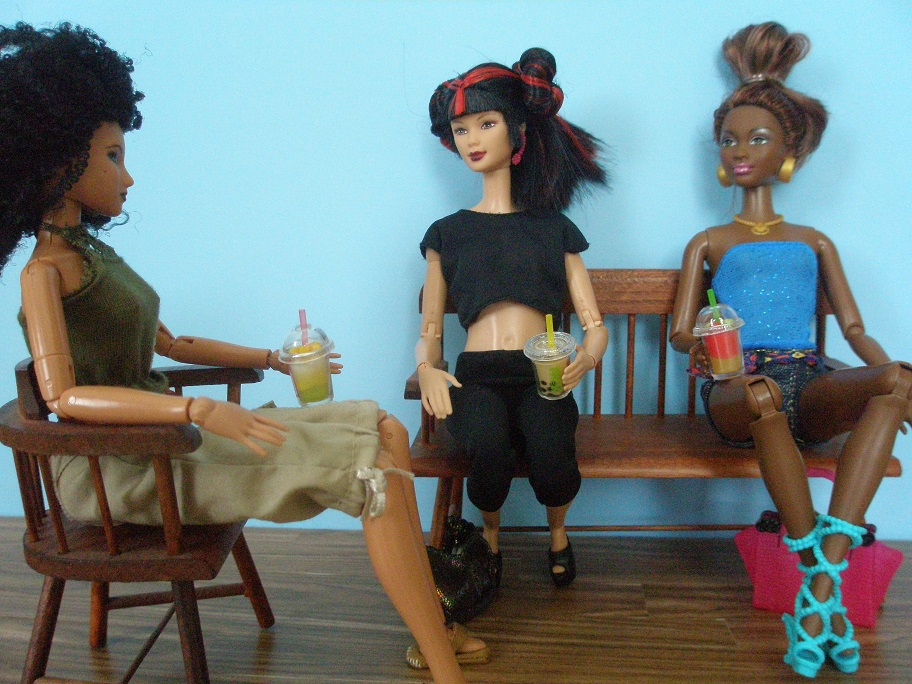 Three dolls seated, dressed in capris, yoga pants, shorts, and sleeveless tops. Each is holding a clear plastic cup of bubble tea or frozen drink.