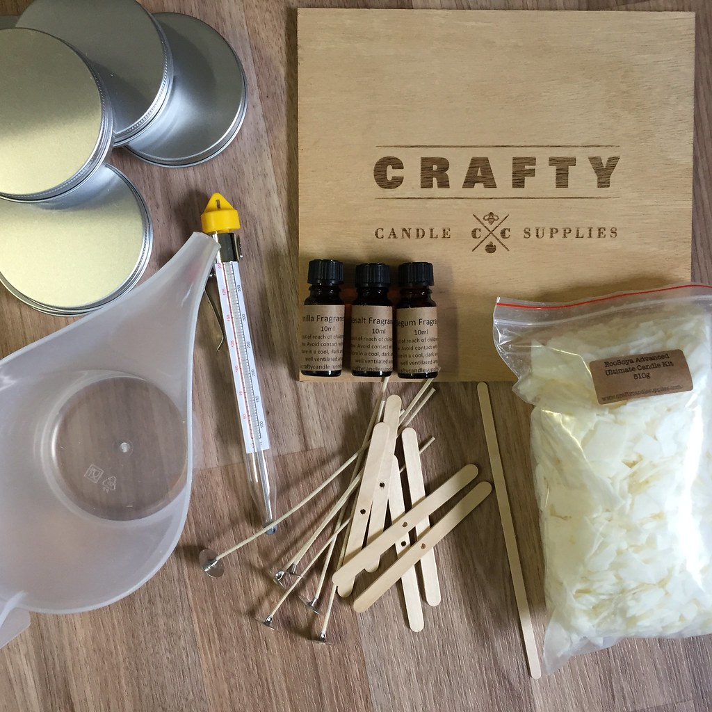 flat lay showing everything in the kit, wicks, tin, soy flakes, thermometer, fragrances and a jug