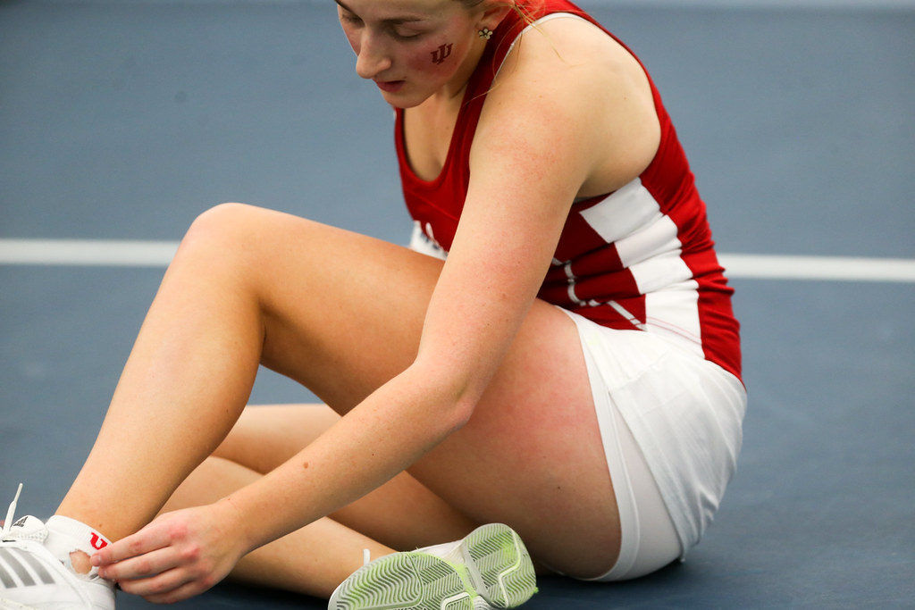 Indiana's Kim Schmider tends to her ankle after falling during her singles match.