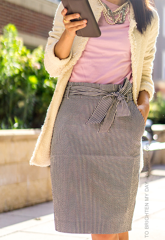 beige tweed jacket, mixed metal necklace, lavender top, striped paperbag pencil skirt with bow sash, taupe clutch