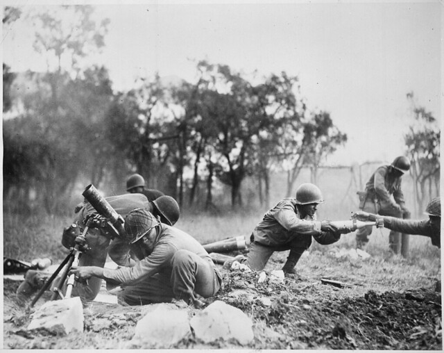 """Members_of_a_Negro_mortar_company_of_the_92nd_Division_pass_the_ammunition_and_heave_it_over_at_the_Germans_in_an_almos_-_NARA_-_535546"