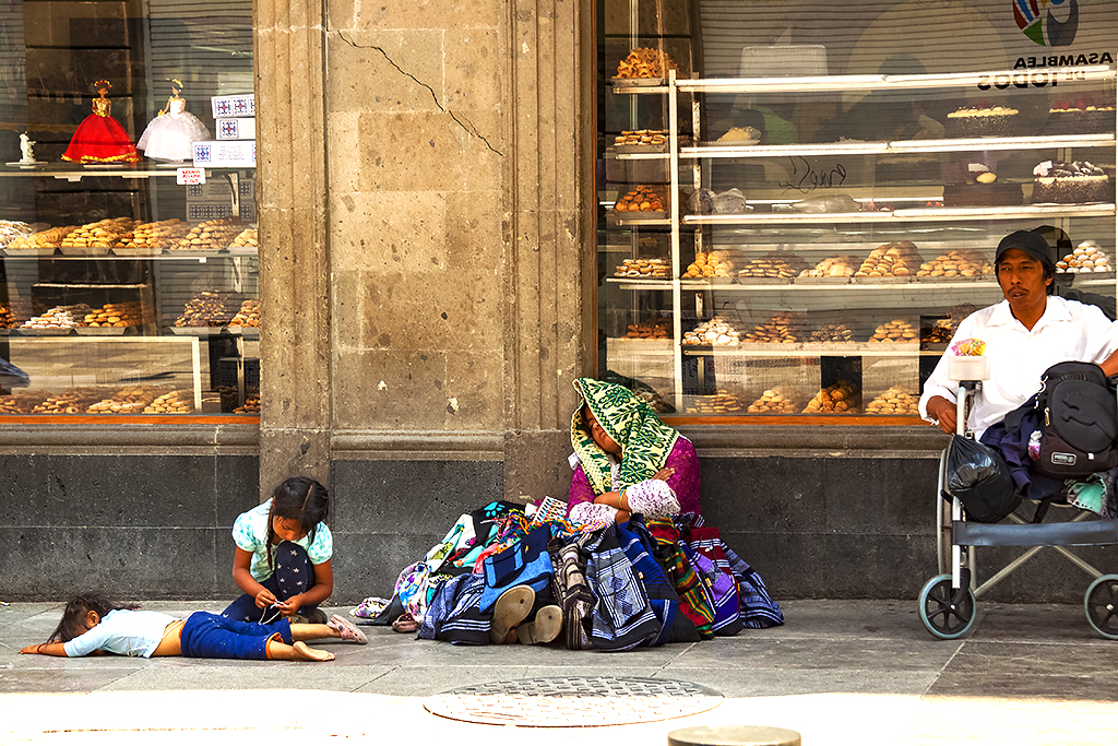 Man on wheelchair, woman and small children on sidewalk outside fancy bakery--Mexico City
