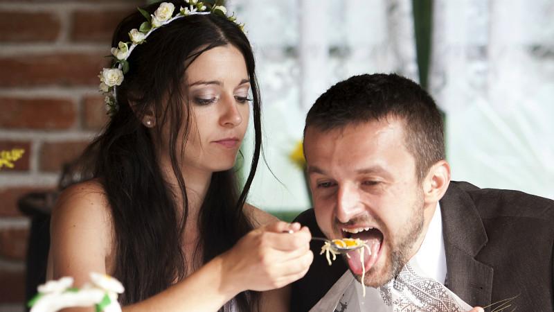 A bride feeding a groom.
