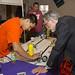 Lab Director Charlie McMillan listens as STEM student Christian Cordova (left) demonstrates his team's robotics project.