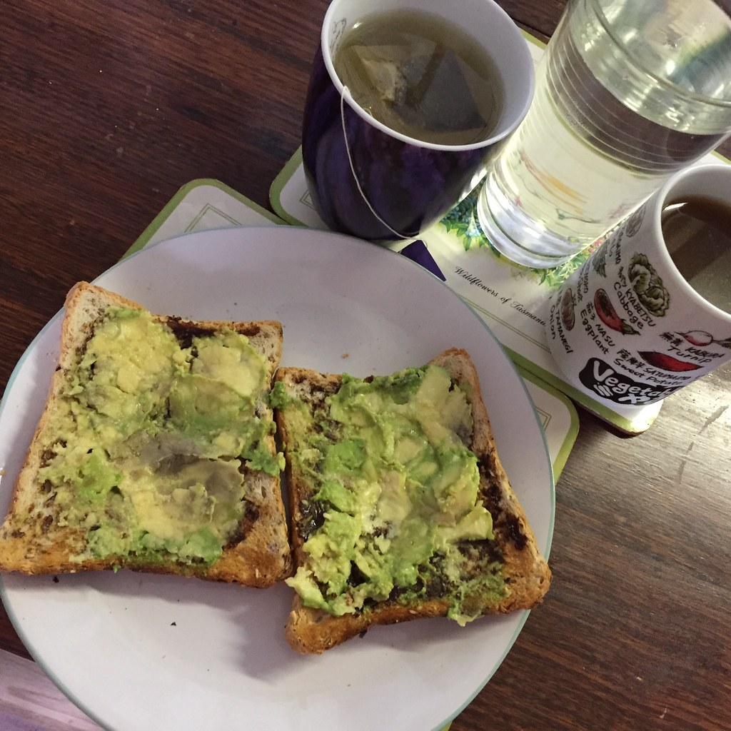 avocado on toast with a cup of tea, big glass of water and a mug of broth