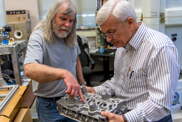 Mike Crumpler and Tony Overfelt examine metal components in the lab.