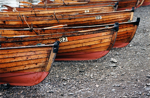 Wooden boats all lined up on a beach in England's Lake District