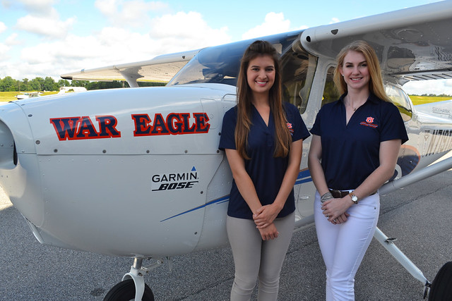 Kendall Higdon and Ashley Tucker stand next to a Cessna Skyhawk 172 airplane.