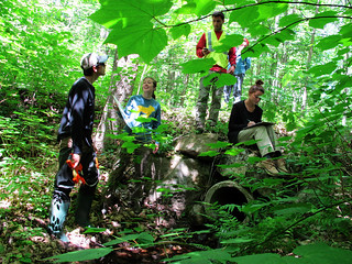 a picture of four interns in the woods, collecting data on a culvert