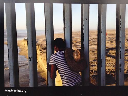 一名墨西哥人透过美墨边境墙向美国一侧张望