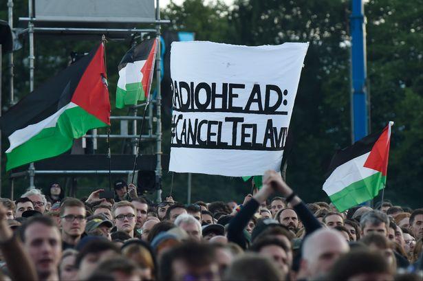 在蘇格蘭GLASGOW音樂會上,在場有支持巴勒斯坦BDS運動的民眾揮舞巴勒斯坦旗幟,向Radiohead表達取消在特拉維夫演出行程的訴求。(攝影:ANDY BUCHANAN/AFP)