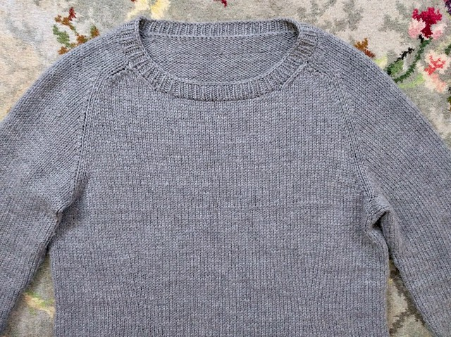 Grey handknit jumper with saddle/raglan hybrid shoulders.