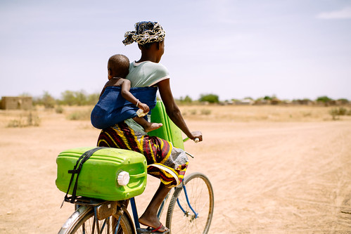 Barry Aliman, 24 years old, rides her bicycle with her baby to collect water for her family