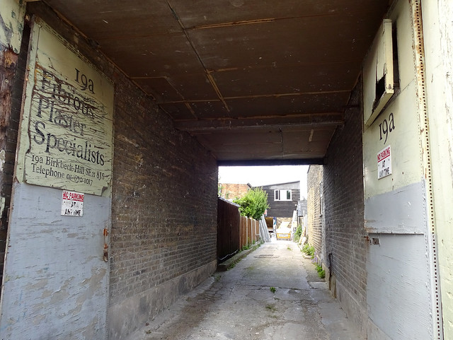 "A view through a square brick-lined tunnel to an open passageway and buildings at the far end.  A dilapidated sign on the left wall reads ""19a / E J Harman & Co Ltd / Fibrous Plaster Specialists / 19a Birkbeck Hill SE21 8JS""."