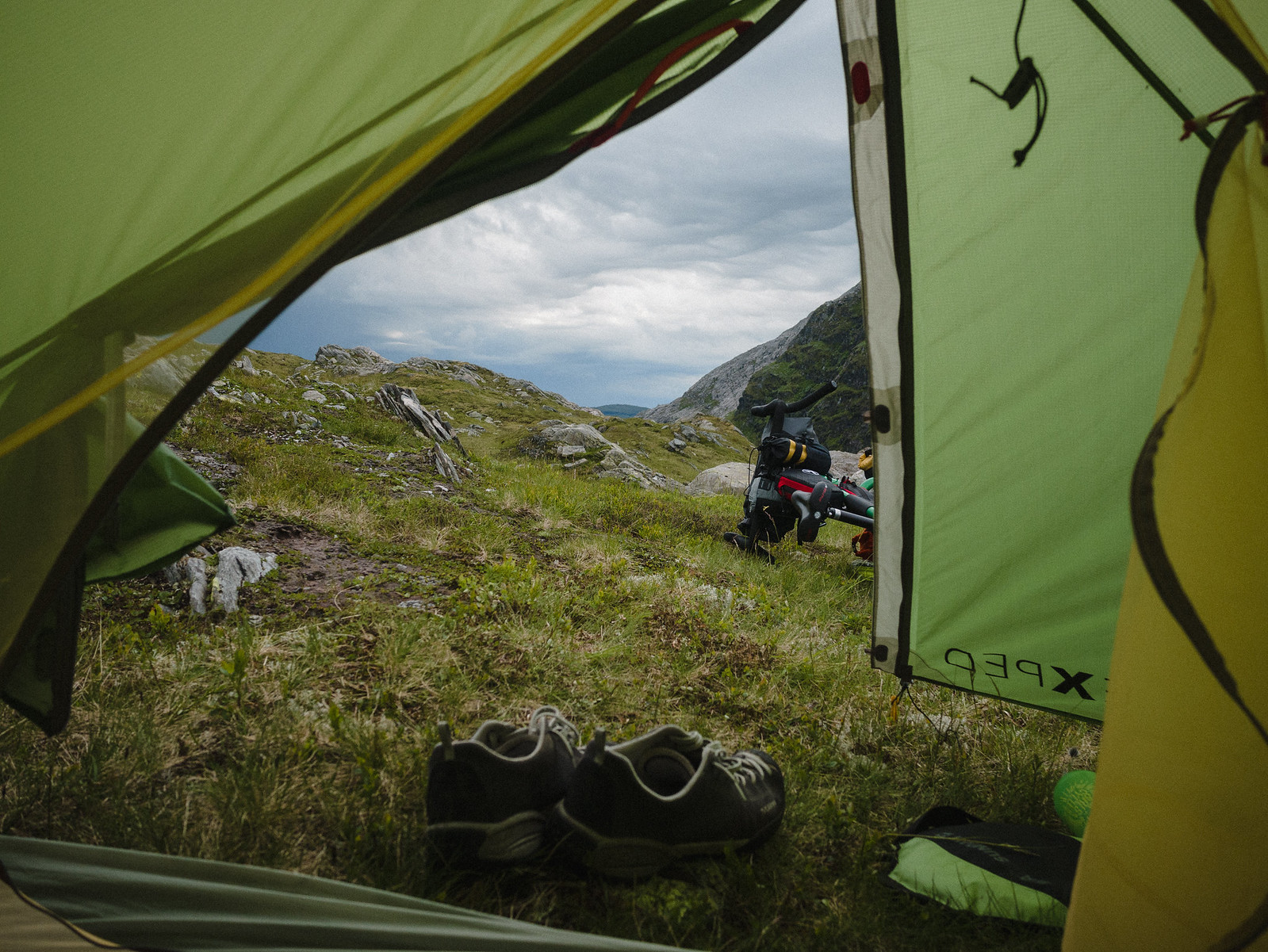 View out of a tent, mountain landscape, shoes and a touring bicycle.