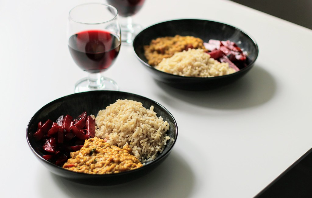 Beetroot curry with dhal & rice in bowls. Glasses of red wine