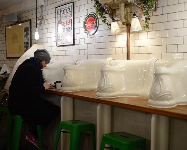 Mujer tomando un café en uno de los retretes de Attendant