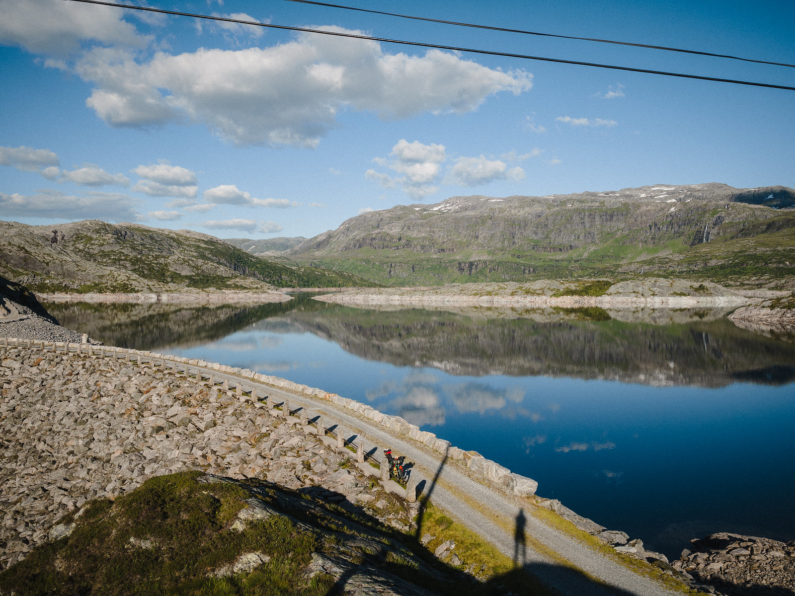 Dam, reservoir and distant mountains. Bicycle and a man's shadow on the road over the dam.