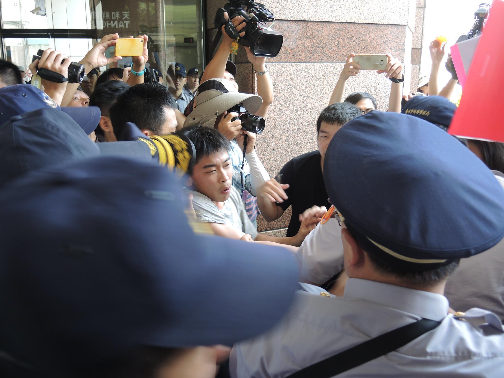 青年團體擠向民進黨部一樓玻璃門,遭優勢警力強制阻擋。(攝影:曾福全)