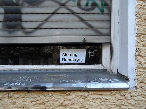 """Schild in einem Fenster mit fast heruntergelassenem Rollladen: """"Montag Ruhetag"""""""