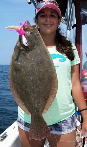 Photo of: Woman on boat holding a flounder