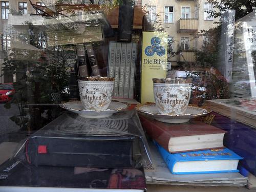 """Zwei Kaffeetassen aus der Zeit um 1900 mit der Aufschrift """"Zum Andenken"""" in Goldbuchstaben im Schaufenster eines Antiquariats"""