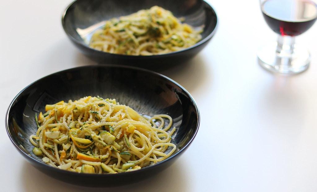 Spaghettini con zucchini in bowls with glass of wine